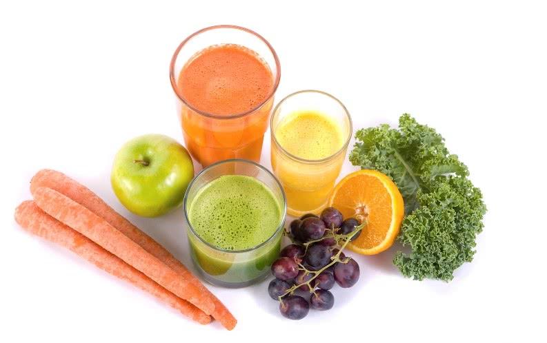 Салат, яблоко, апельсин, виноград, морковь и соки в стаканах