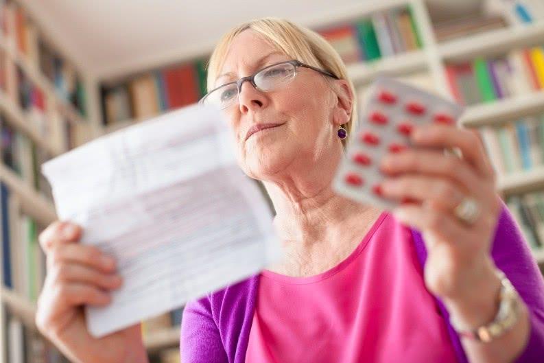 Женщина читает инструкцию к препарату