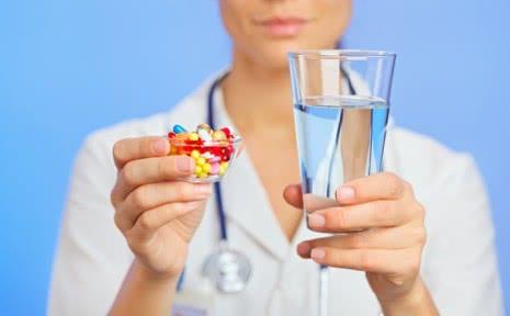 Лекарственные препараты и стакан с водой в руках врача