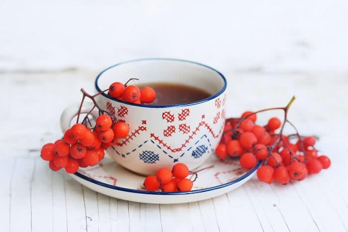 Ягоды и отвар красноплодной рябины в чашке