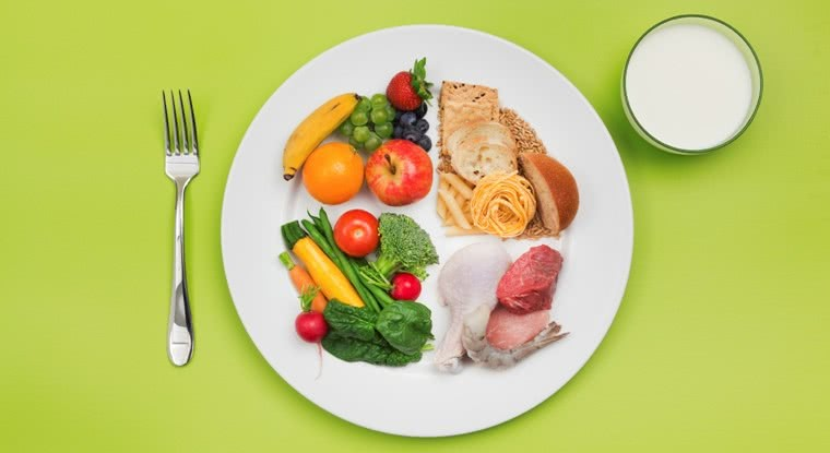 Злаки, фрукты, овощи и мясо на тарелке, вилка и напиток в стакане