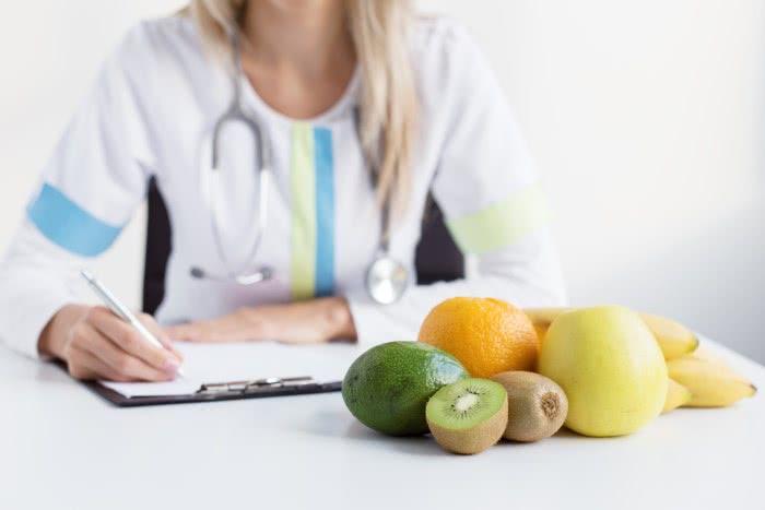 Диета при остром колите, доктор, делающий записи, и фрукты на столе